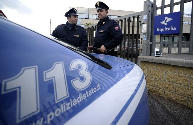 Italian police officers stand outside th